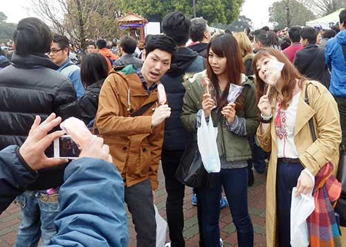 People posing with their still wrapped penis lollipops at Kawasaki Daishi Park, Kawasaki, Kanagawa
